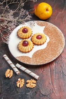 暗い床のケーキの甘いビスケット砂糖のプレート内の正面図おいしい小さなクッキー