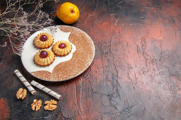 Вид спереди вкусное маленькое печенье внутри тарелки на темном столе, торт, сладкое печенье, сахар