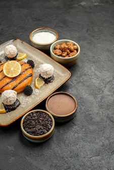 正面図ダークグレーの背景にココナッツキャンディーとおいしい小さなパイケーキティービスケットクッキー甘いキャンディー