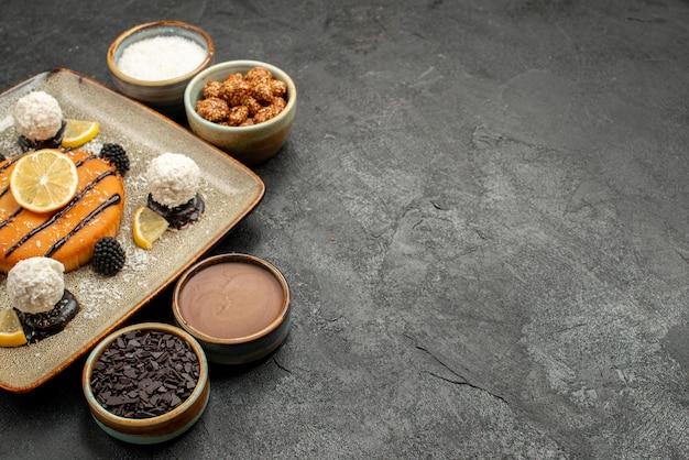 正面図ダークグレーの背景にココナッツキャンディーとおいしい小さなパイケーキティービスケットクッキー甘いキャンディー 無料写真