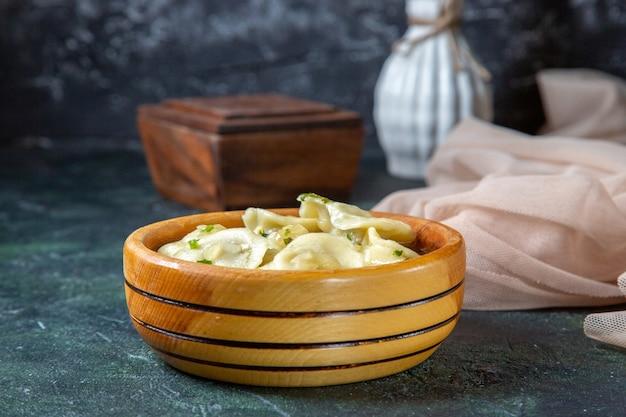 Front view yummy meat dumplings inside wooden plate on dark surface