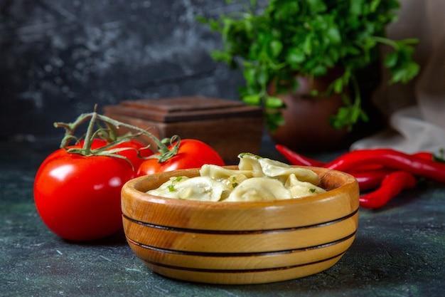 Gnocchi di carne gustosi vista frontale all'interno del piatto di legno con pomodori freschi sulla superficie scura
