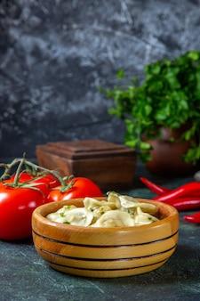 暗い表面に新鮮なトマトが付いている木の板の中の正面図おいしい肉餃子