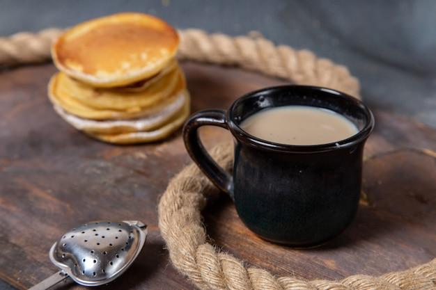 Muffin gustosi vista frontale deliziosi e al forno con tazza nera di latte sullo zucchero dolce sfondo grigio cibo colazione pasto
