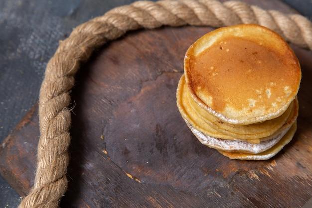 Muffin squisiti di vista frontale delizioso e cotto sullo zucchero dolce del pasto della colazione dell'alimento della scrivania di legno
