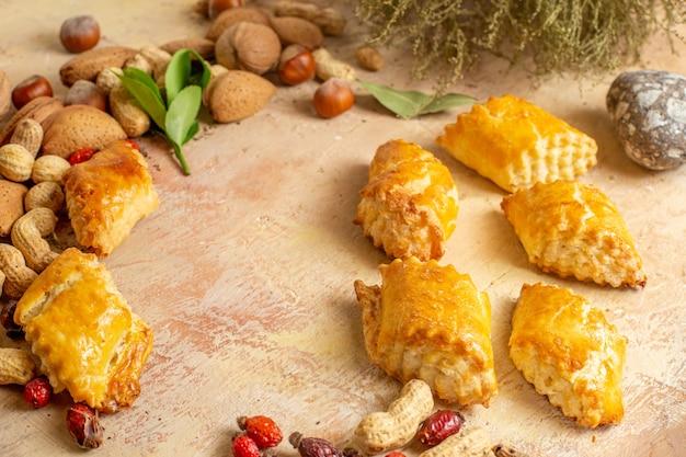正面図茶色の机の上の新鮮なナッツとおいしいナッツペストリーペストリーパイ甘いケーキナッツ