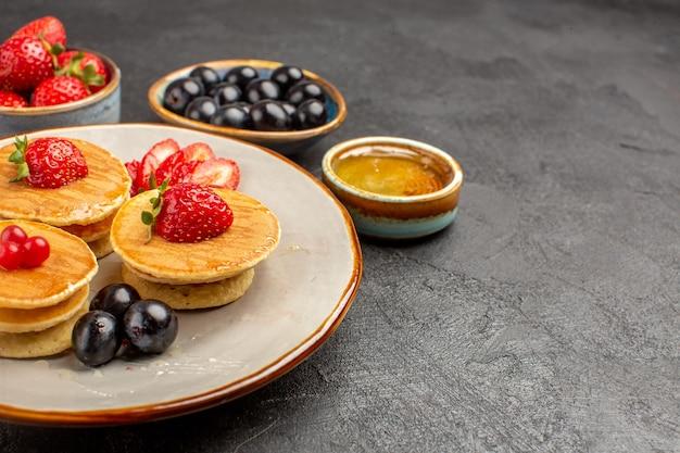 Frittelle squisite di vista frontale poco formate con frutti su una torta di torta di superficie grigia