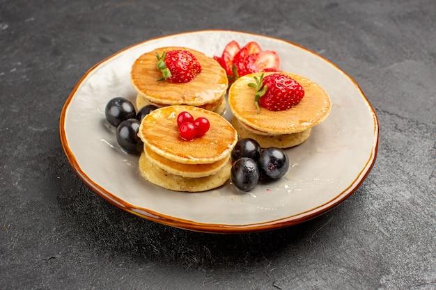 Вид спереди вкусные блины, немного сформированные с фруктами на темной поверхности фруктовый пирог с пирогом