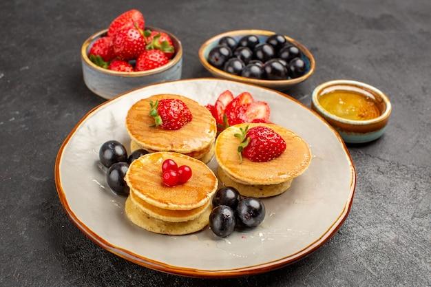 Вкусные блины, немного сформированные с фруктами на серой поверхности пирога, фруктовый торт, вид спереди