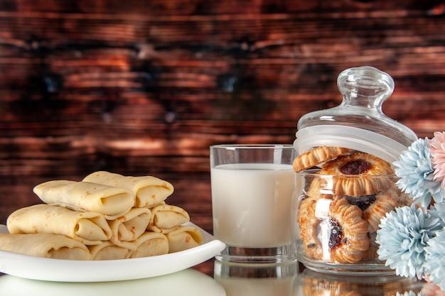 正面図茶色の背景にビスケットとミルクのおいしいパンケーキ砂糖デザート食事クッキー朝食ケーキ朝の色甘い