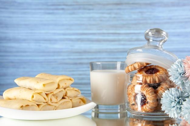 正面図明るい背景の上のビスケットとミルクとおいしいパンケーキケーキ砂糖デザート食事クッキー朝食朝の色甘い