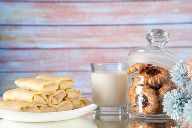 正面図明るい背景にビスケットとミルクのおいしいパンケーキ砂糖デザートカラークッキー甘い朝食食事ケーキ朝