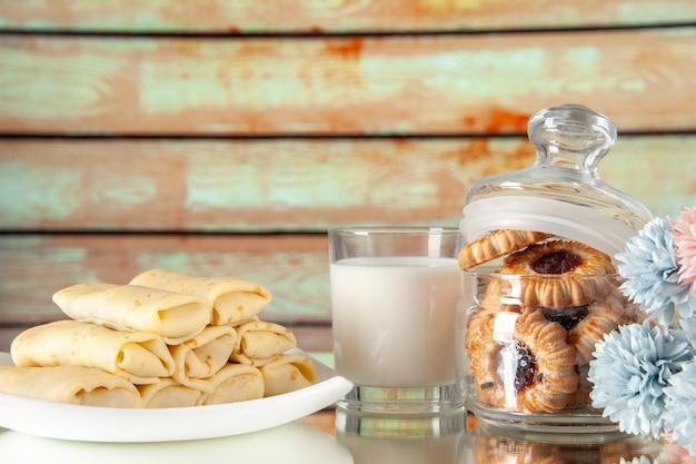 正面図明るい背景にビスケットとミルクのおいしいパンケーキ砂糖デザート食事クッキー朝食ケーキ朝の色甘い