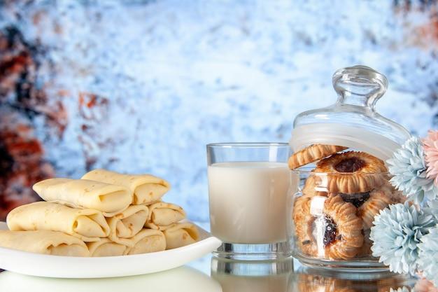 正面図明るい背景にビスケットとミルクのおいしいパンケーキ砂糖デザート食事クッキー甘い朝食ケーキ朝の色