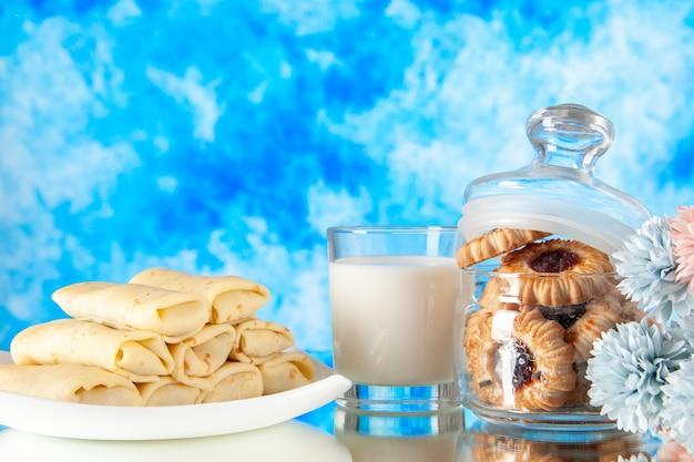 밝은 파란색 배경에 비스킷과 우유를 곁들인 맛있는 팬케이크 설탕 디저트 식사 쿠키 달콤한 아침 케이크 아침 색상