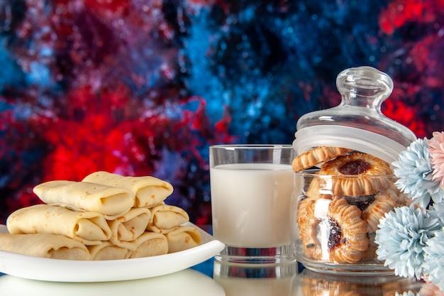 正面図濃い赤の背景にビスケットとミルクのおいしいパンケーキ砂糖デザートミールクッキー甘い朝食ケーキ朝の色
