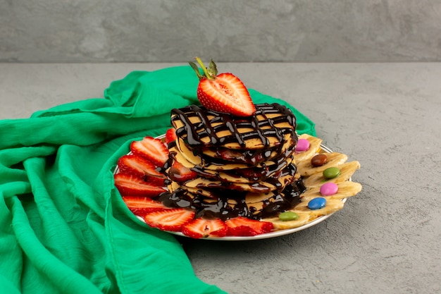Front view yummy pancakes with chocolate sliced red strawberries and bananas inside white plate on the grey floor