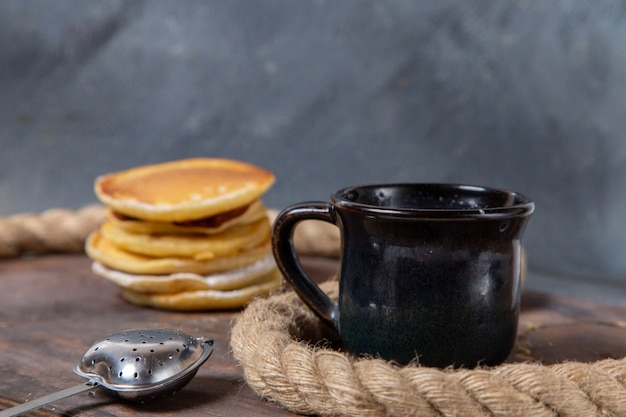 Вид спереди вкусные блины с чашкой молока на сером фоне сладкая еда сахарная еда завтрак
