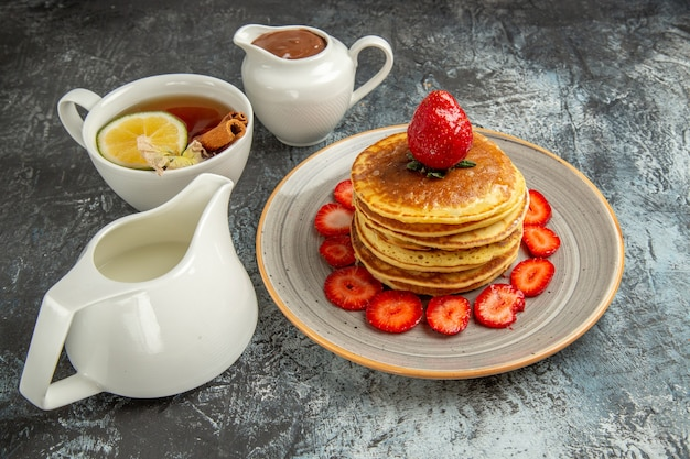 Front view yummy pancakes with cup of tea and fruits on light surface fruits cake sweet
