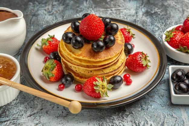 明るい表面のフルーツケーキの甘い上に新鮮な果物と蜂蜜の正面図おいしいパンケーキ