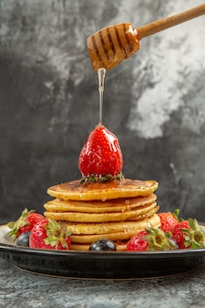 Front view yummy pancakes with fresh fruits on the light surface breakfast sweet fruit