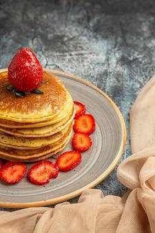 正面図明るい表面のケーキの甘い果物に新鮮なイチゴとおいしいパンケーキ