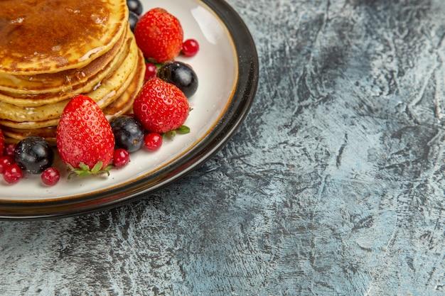 明るい床の朝食の甘い果物に果物と蜂蜜の正面図おいしいパンケーキ