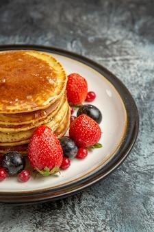 正面図明るい表面の朝食の甘い果物に果物と蜂蜜とおいしいパンケーキ