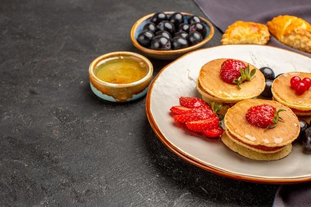 暗い表面の甘いフルーツケーキにフルーツとオリーブの正面図おいしいパンケーキ