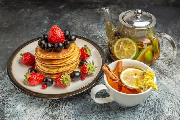 明るい表面のフルーツの甘い朝食にフルーツとお茶を添えた正面図のおいしいパンケーキ