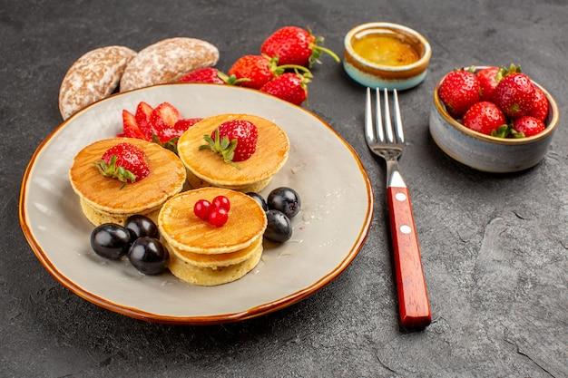 Frittelle gustose vista frontale con frutta sulla torta torta di frutta superficie scura dolce