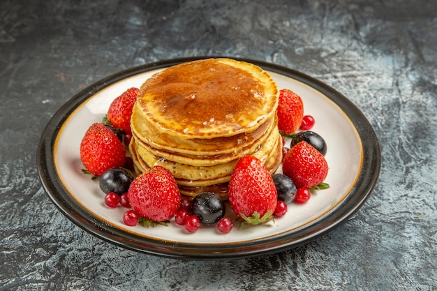 Front view yummy pancakes with fruits and honey on a light surface breakfast sweet fruit