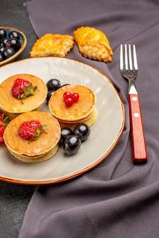 Frittelle gustose vista frontale con frutta e olive sulla torta di frutta dolce superficie scura
