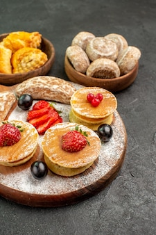 Front view yummy pancakes with fruits and sweet cakes on the dark surface sweet cake dessert