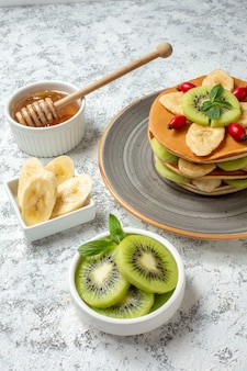 白い表面に蜂蜜とスライスした果物の正面図おいしいパンケーキ