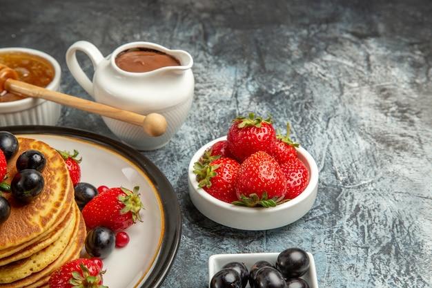 Frittelle gustose vista frontale con miele e frutta sulla torta di frutta superficie leggera dolce