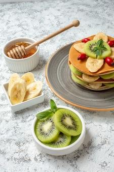 Vista frontale gustose frittelle con miele e frutta a fette sulla superficie bianca