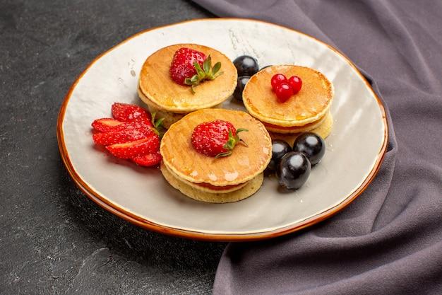 Frittelle squisite di vista frontale con olive e frutta sulla torta dolce della frutta di superficie scura