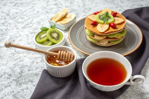 Vista frontale gustose frittelle con frutta a fette e tazza di tè su superficie bianca frutta dolce dessert colazione colore torta zucchero