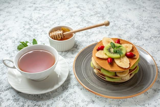 Vista frontale gustose frittelle con frutta a fette e tazza di tè su superficie bianca frutta dolce dessert zucchero colazione torta colorata