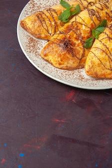 Вкусная выпечка, вид спереди с глазурью внутри тарелки на темном пространстве