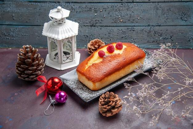 Vista frontale torta gustosa lunga formata sullo sfondo scuro torta biscotto zucchero biscotto torta tè dolce