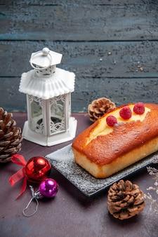 Vista frontale torta gustosa lunga formata su sfondo scuro torta biscotto zucchero biscotti torta dolce tè
