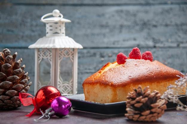 Vista frontale torta gustosa lunga formata sul pavimento scuro torta biscotto zucchero biscotto torta tè dolce