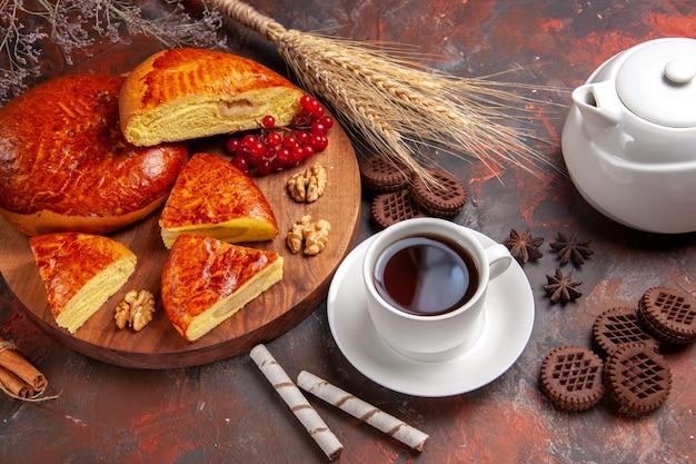 Вкусные пироги, нарезанные чашкой чая на темном столе, сладкий пирог, вид спереди