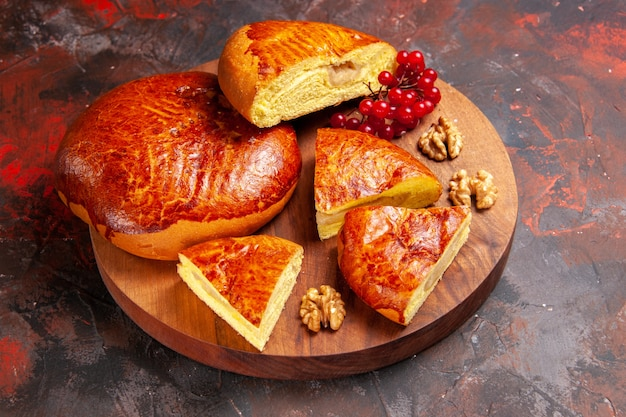 Torte gustose vista frontale affettate con bacche rosse sul dolce della torta della pasticceria della torta della tavola scura