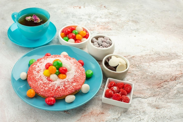 Front view yummy pink cake with colorful candies and cup of tea on white background dessert pie rainbow color cake candy Free Photo