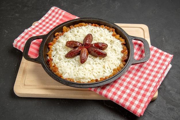 Vista frontale gustoso piatto di riso cotto plov con uvetta diversa su superficie scura piatto di uvetta cibo olio per cena di riso