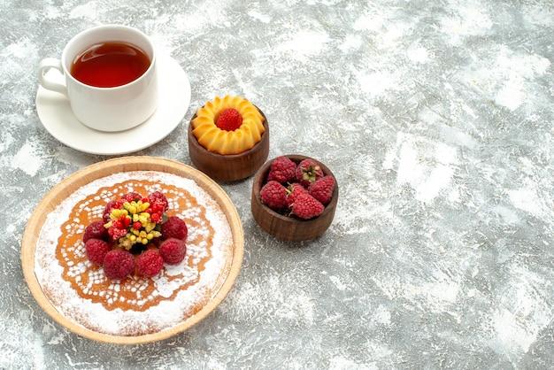 正面図白い背景の上のお茶とおいしいラズベリーケーキビスケットティー甘いパイケーキ砂糖