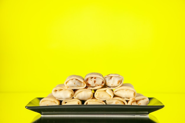 Front view yummy rolled pancakes inside plate on yellow background sugar morning breakfast sweet color dessert cake milk